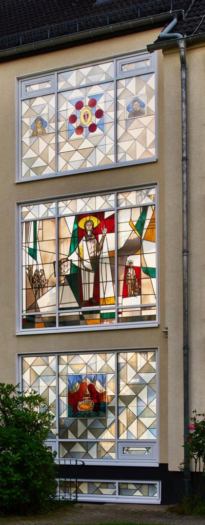 Fenster im Provinzhaus der Vinzentinerinnen in Köln-Nippes, Einrahmung mit Motiven von Clemens Hillebrand. Mitteleres Fenster von Will Thonnet.